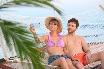 Young couple taking selfie in hammock on beach