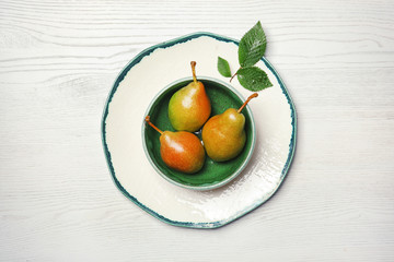 Dishware with pears on wooden background, top view