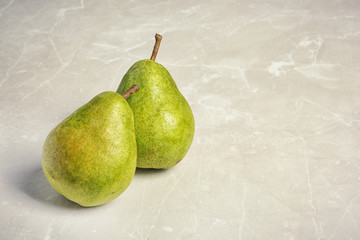 Ripe pears on grey background. Space for text