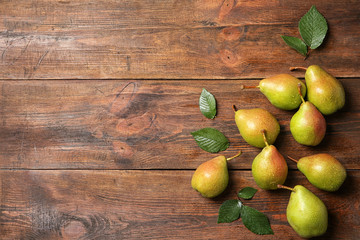 Ripe pears on wooden background, top view. Space for text