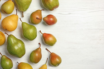 Ripe pears on white wooden background, top view. Space for text