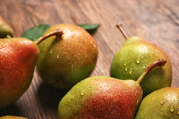 Tasty ripe pears on wooden table, closeup