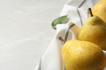 Ripe pears and striped fabric on grey background, closeup. Space for text