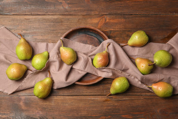 Flat lay composition with ripe pears on wooden background