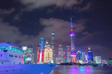 Ship by illuminated Shanghai downtown