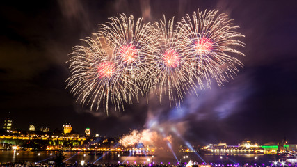 Big and bright fireworks with many colors in front of Quebec City during a summer festival.