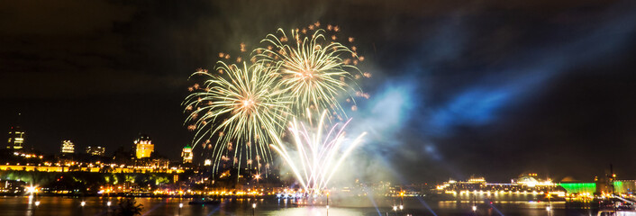 (Panoramic) White and green fireworks in front of Quebec City during a summer festival.