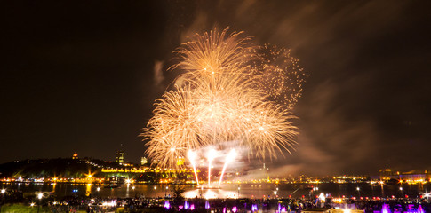 Golden fireworks in a dark sky over the water of a big river in Quebec, Canada.