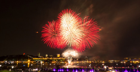 White and red fireworks over the Saint-Lawrence River near Quebec City during a Canadian summer festival.