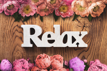 """word """"relax"""" on wooden background with many flowers"""