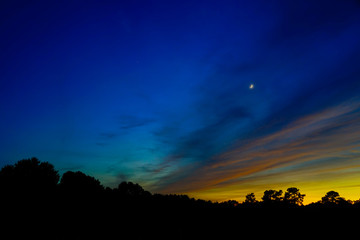 A dramatic vivid blue night sky at sundown with yellow cloud streaks and a small moon. Copy space.
