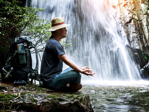 male hiker doing yoga on rock near waterfall