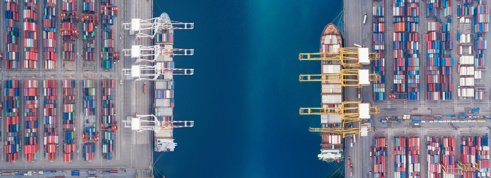 Aerial view panoramic sea port warehouse and container ship or crane ship working for delivery containers shipment. Suitable use for transport or import export to global logistics concept.