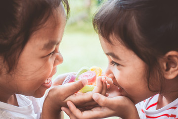 Two asian child girls holding sweet candies in thier hands and share to each other Wall mural