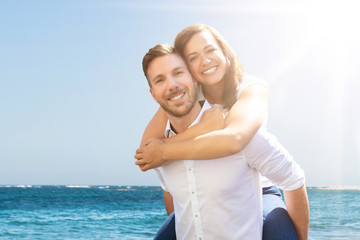 Happy Man Giving Piggyback To His Wife At Beach