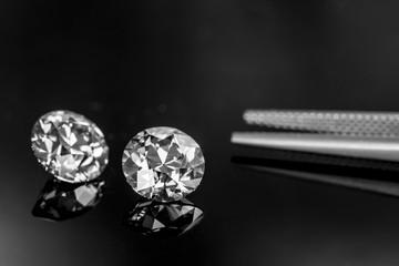 Diamonds with tweezers on background