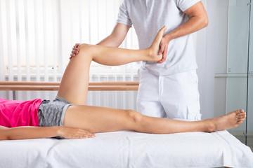 Male Therapist Stretching Woman's Leg