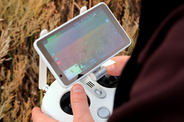 Hands of a man on the joystick control panel of an unmanned aerial vehicle. The farmer controls the drones and sees a field with a wheat crop on the screen.
