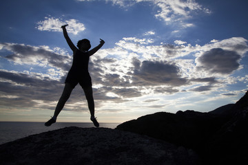 Woman jumping on cliffs in sunset