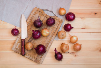 Onions on cutting board and near on wooden background. Top view.