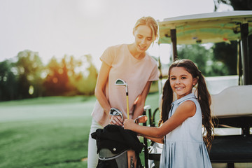 Young Mother and Daughter with Cart on Field.