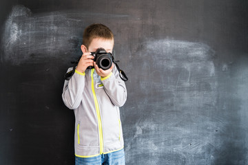 Young boy's shooting with photo camera near blackboard. Young photographer. Creative design concept for 2019 calendar.