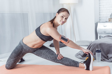 Flexible body. Nice positive woman touching her feet with a hand while showing how to do an exercise