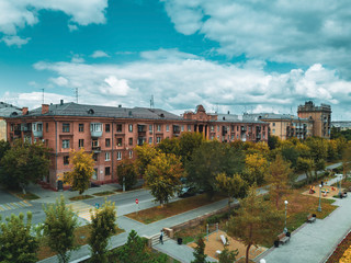 Aerial panoramic view of rest area and old classic building with various decor elements of building facade (columns, arches, pediments, bas-reliefs, consoles), cloudy autumn day in Magnitogorsk