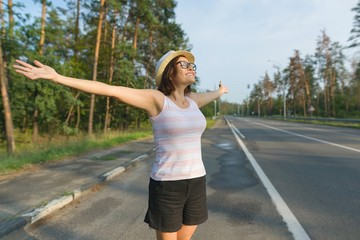 Smiling mature woman stands on the road, spread her arms out to the sides, enjoying freedom and sunset