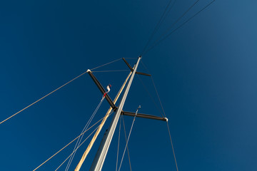 Detail of mast on sailing boat with blue sky in the background