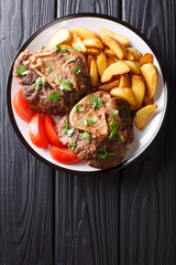 shank Ossobuco with a garnish of fried potato slices and fresh tomatoes close-up on a plate. Vertical top view