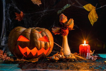 Halloween photo of table with pumpkin, biscuits, dried flowers, burning candle