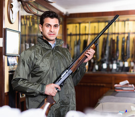 Confident hunter male wearing windbreaker in hunting shop with rifle in hands