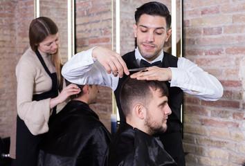 Hairdresser man doing styling of guy