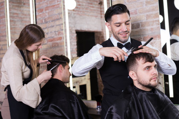 Barber making haircutting for male client