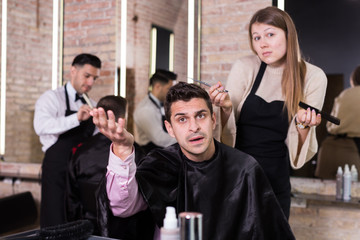Unpleasantly surprised man with regretting woman hairdresser in salon