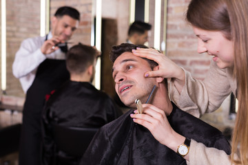 Woman barber shaving client with straight razor