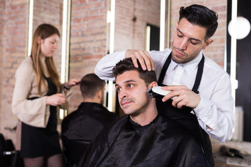 Man barber making hairstyle for male with electric trimmer