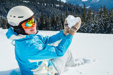 woman in a blue ski suit and mask on top of a mountain holding a snow in the shape of a heart