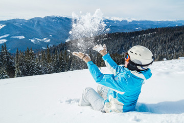 a woman in a blue ski suit and mask hurls snow at the camera on top of the mountain.