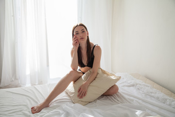 brunette woman after sleeping in bedroom pillows on the bed