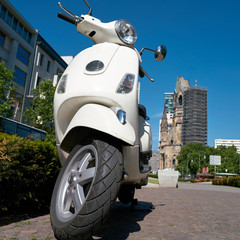 Geparkter Motorroller in der Innenstadt von Berlin. Im Hintergrund befindet sich der Breitscheidplatz mit der Gedächtniskirche.