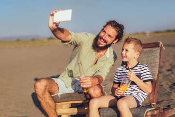 Shot of father and son taking selfie at the beach. Young man with little boy making self portrait using smart phone at the sea shore.
