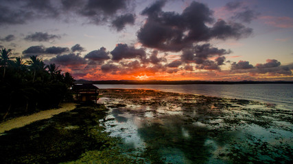 sunset over ocean 101 siargao philippines clouds water low palm trees