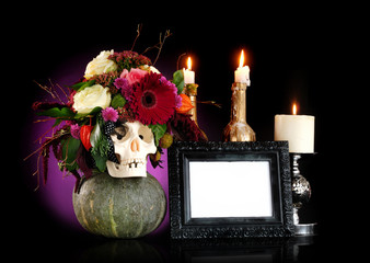 Still life of skull decorated with flowers, burning candles and frame