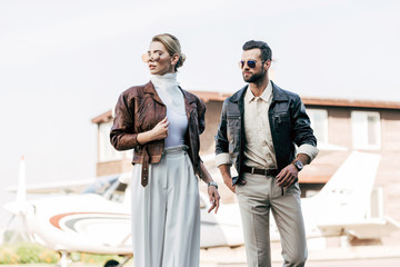 stylish couple in sunglasses and leather jackets standing near airplane