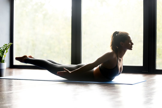 Young sporty woman practicing yoga, doing Double Leg Kicks exercise, Salabhasana pose, working out, wearing sportswear, grey pants and top, indoor full length, yoga studio