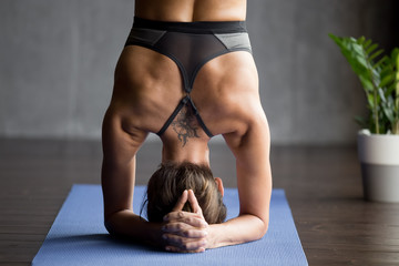 Young sporty attractive woman practicing yoga, doing headstand exercise, variation of salamba sirsasana pose, working out, wearing sportswear, grey top, indoor close up view, yoga studio, rear view