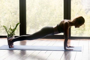 Young sporty woman practicing yoga, doing Push ups or press ups exercise, phalankasana, Plank pose, working out, wearing sportswear, grey pants and top, indoor full length, yoga studio. Side view