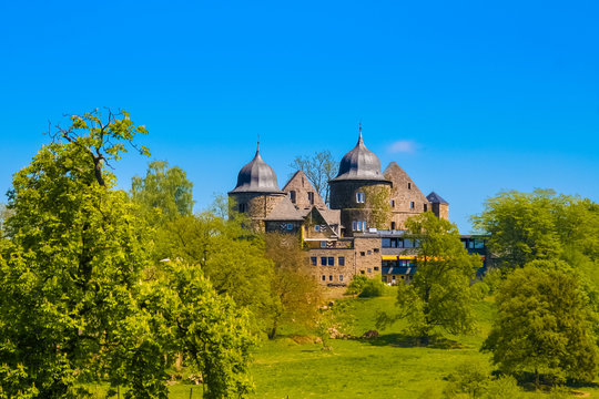 Great view of the west side of Sababurg also known as the Sleeping Beauty Castle, lying on a hilltop in the magnificent forest Reinhardswald in North Hesse, Germany.